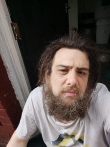 Student campaign: A man with dark hair and a beard wearing a white t-shirt sits in a doorway looking up at the camera