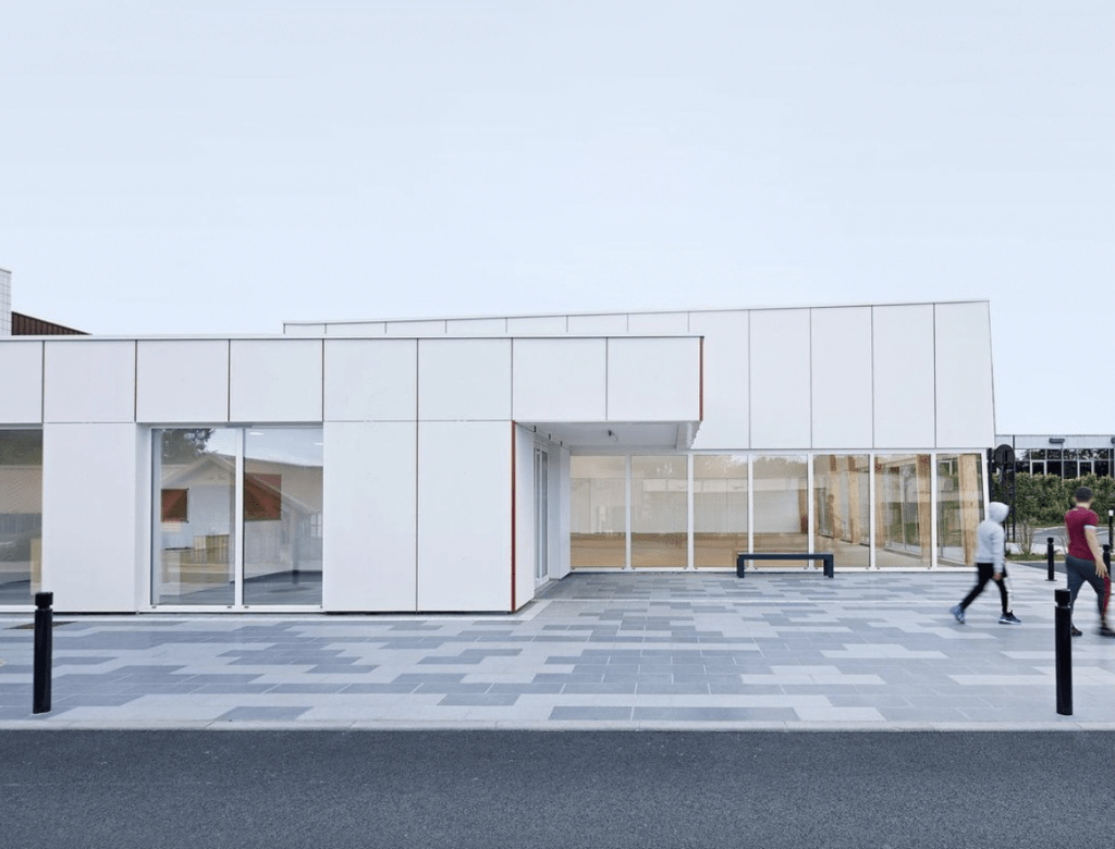 Hempcrete: The exterior of a sports hall in paris clad in white. Its a low square building