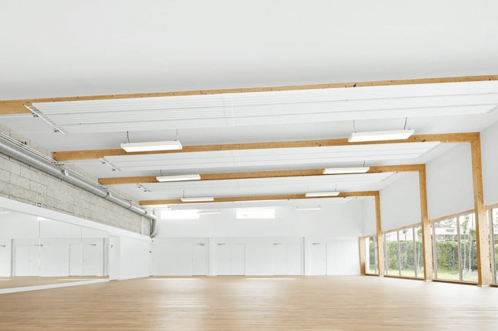 Hempcrete: The interior of a white sports hall with blonde wood floors and light from the windows on the right side