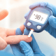 Diabetic neuropathy: a diabetic person testing their glucose levels on a blue blood sugar monitor
