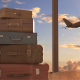Emigration: A stack of suitcases against a window revealing a sunset and a plane