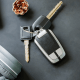 Driving: A set of grey keys on a grey background next to a pine cone and grey headphones