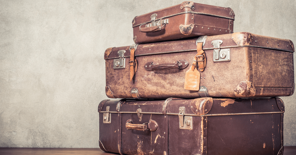 Canna-emigration: a pile of three brown suitcases in a brown room
