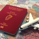 Canna emigration: An Irish passport lying on a map with a small toy airplane next to it
