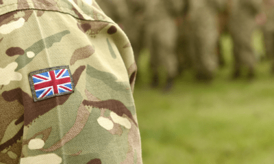 Veterans and CBD: The shoulder of an army person wearing green combat gear with a British flag. on it
