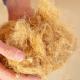 Hemp fibre insulation: A person holding a ball of insulation made from yellow hemp