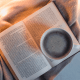 Cannabis books: A book lying on a throw with a cup of black coffee
