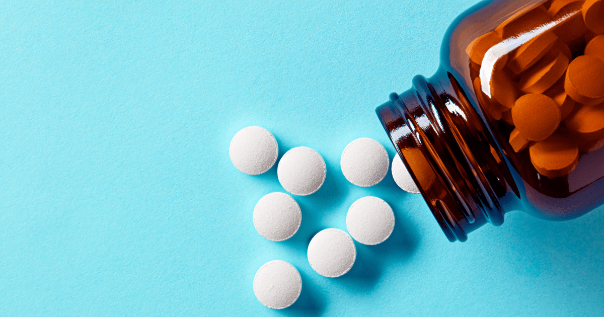 Anti seizure medication: A brown pill bottle on its side with white pills spilling out against a blue background