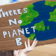 Climate change: A hand holding a sign that says there is no planet B with a painting of an earth on it