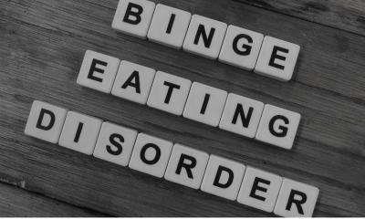 Binge eating: Scrabble tiles spelling out binge eating disorder on a wooden floor