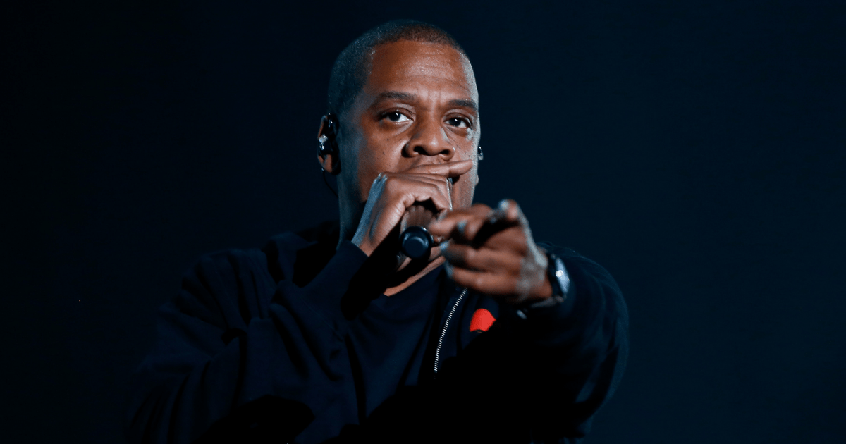 Jay-Z: A photo of the rapper Jay-Z against a black background. He is holding a microphone and rapping into it