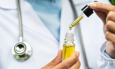 MCAP programme: neurologists holds a yellow bottle of oil with a dropper against a lab coat