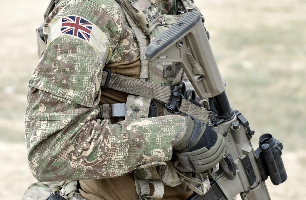 CBD for veterans: A person in an army uniiform holding a machine gun