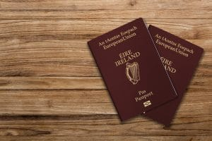 Two red Irish passports lying on a wooden floor