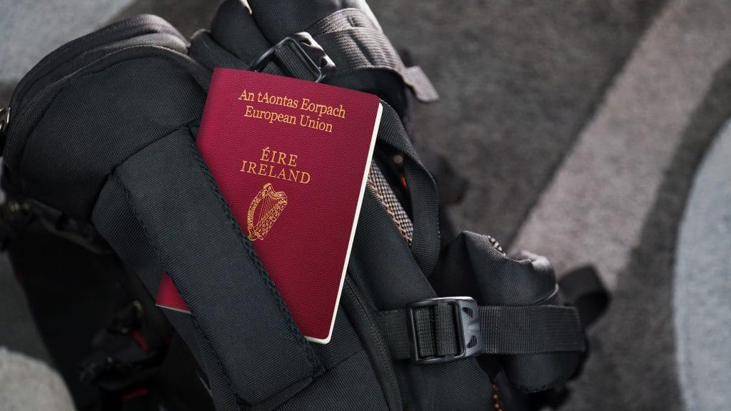Emigration: A red Irish passport sitting on a black bag