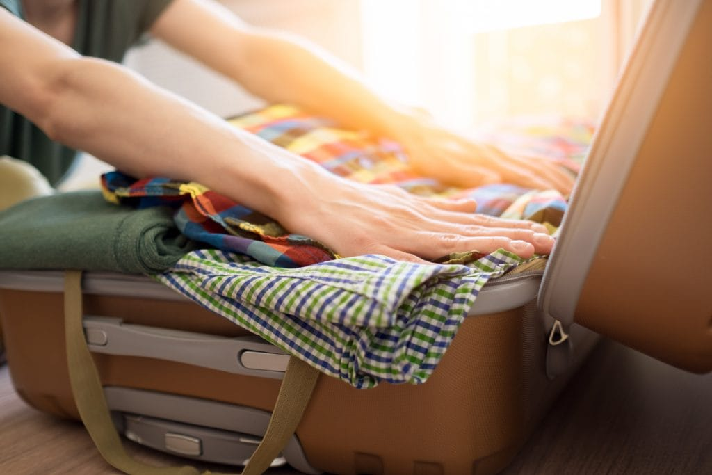 Emigration: two hands packing a suitcase with clothes ready to travel