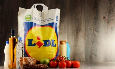 Lidl: A plastic shopping bag on a wooden surface surrounded by milk and oil bottles, tomatos, apples and food items