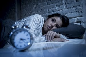 A woman unable to sleep in a bed staring at an alarm clock