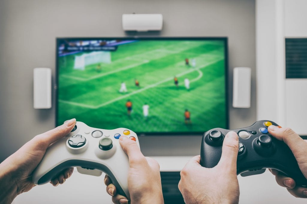 Gaming: Two men holding gaming devices playing a football game on the Tv