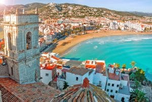 Emigration: The rooftop view of colourful spanish houses overlooking the sea in the sunshine