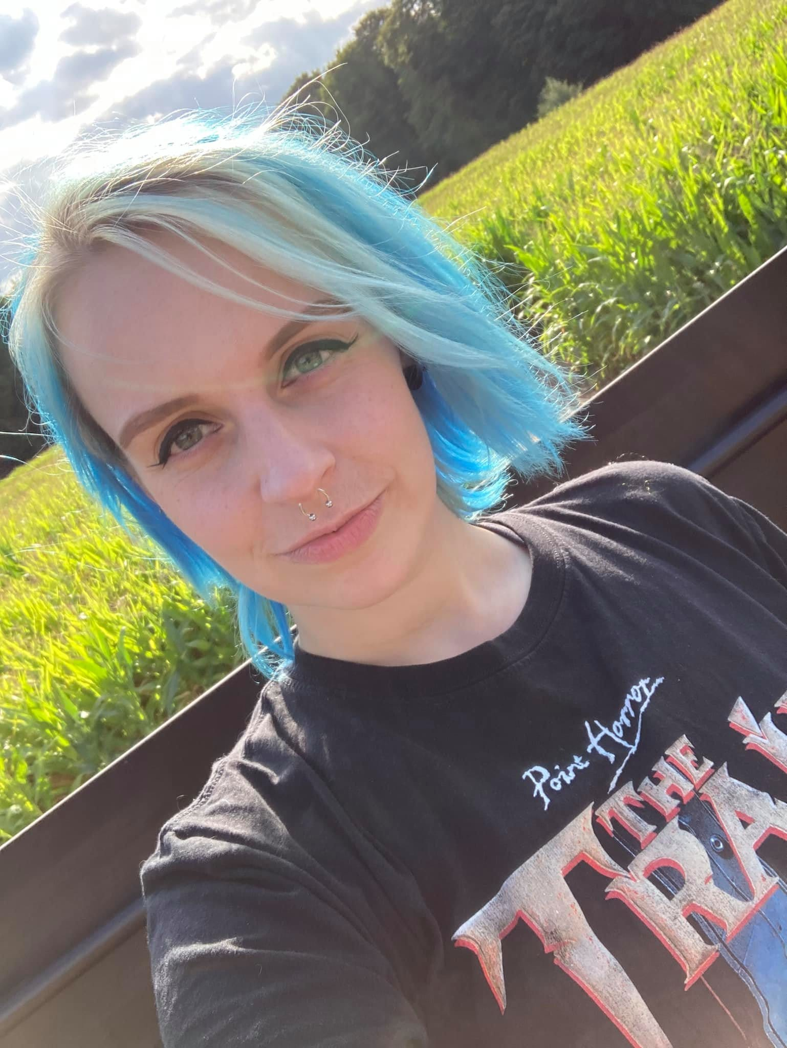 ADHD: A woman with blue shoulder length hair faces the camera wearing a black t-shirt with lettering on it. She is sitting in a corn field