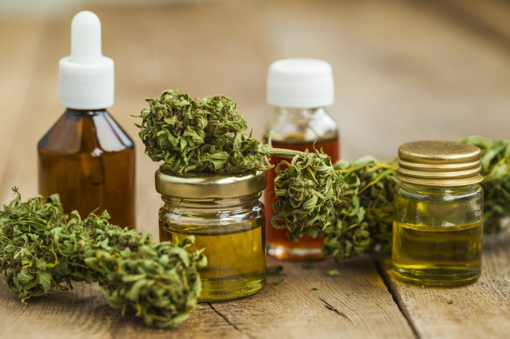 Cancer, cannabis and me: A selection of oil bottles containing yellow oil and cannabis buds