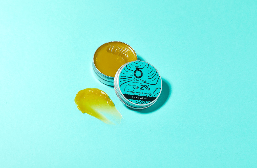 The good level: CBD balm on a blue background with a smudge of balm beside the open tin