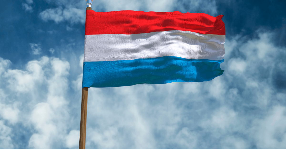 Luxembourg: A flag with red, white and light blue stripes fluttering against a blue sky with white clouds