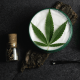 Skin condition: A white cream with a green cannabis leaf on top. It is surrounded by dark oil bottles and a spoon that has cream on it. This is on a dark background