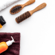 Alopecia: A number of hair products on a white background including two hairbrushes, a bottle of oil, a spray bottle and two towels