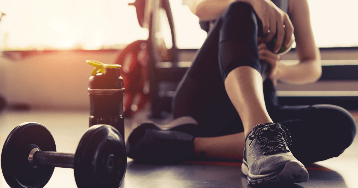 Gym: A woman sits in gym leggings on a wooden floor surrounded by weights