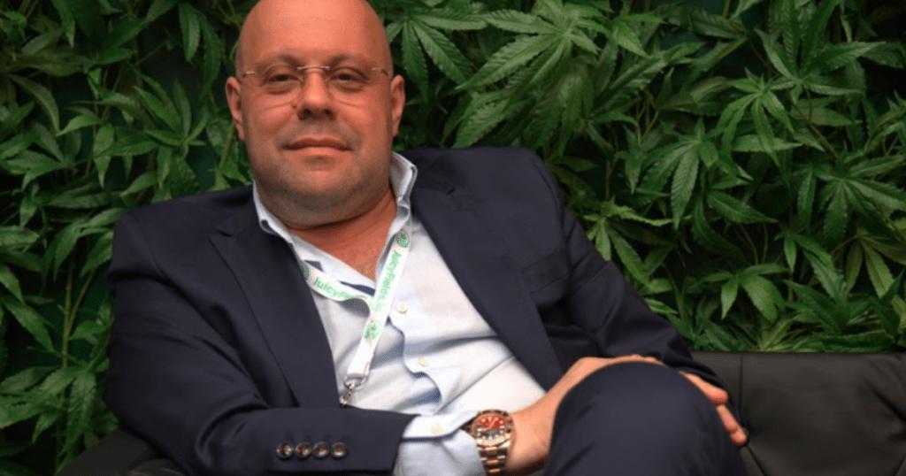 JuicyFields: Alan Ganse the CEO of JuicyFields rests against a wall of hemp plants