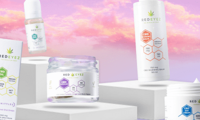 Red Eyez: A collection of CBD jars and bottles against a pink and orange sunset