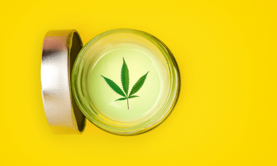 Seizures: A small jar of CBD topical gel on a yellow background. The lid off the jar and it has a cannabis leaf on the top of white cream