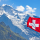 Zurich: A red and white swiss flag against the blue sky of Zurich with mountains