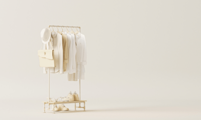 Hemp fashion: A row of white clothing on a single rail in the middle of an all white room. The clothing is all cream or white with a hat perched on the end of the rail
