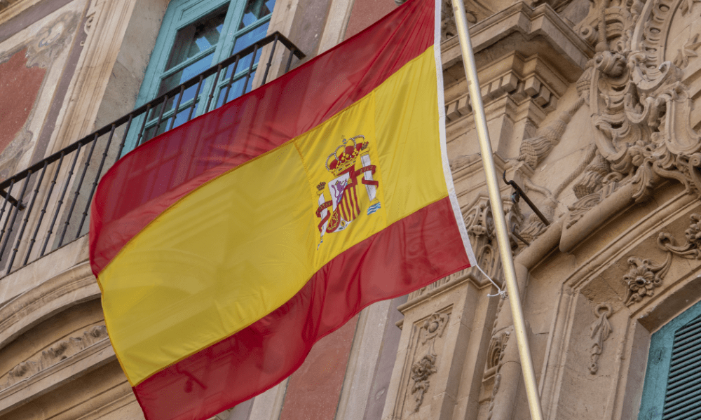 Spain cannabis: A Spanish flag in the air with an old building behind it