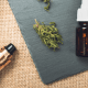 Vaping study: A bottle of oil lies on its side on a grey background. This is resting on a sandy coloured background. There is a vape lying to the left of the image and assorted cannabis buds dotted throughout