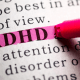 ADHD: A pink pen highlighting the word ADHD in a text