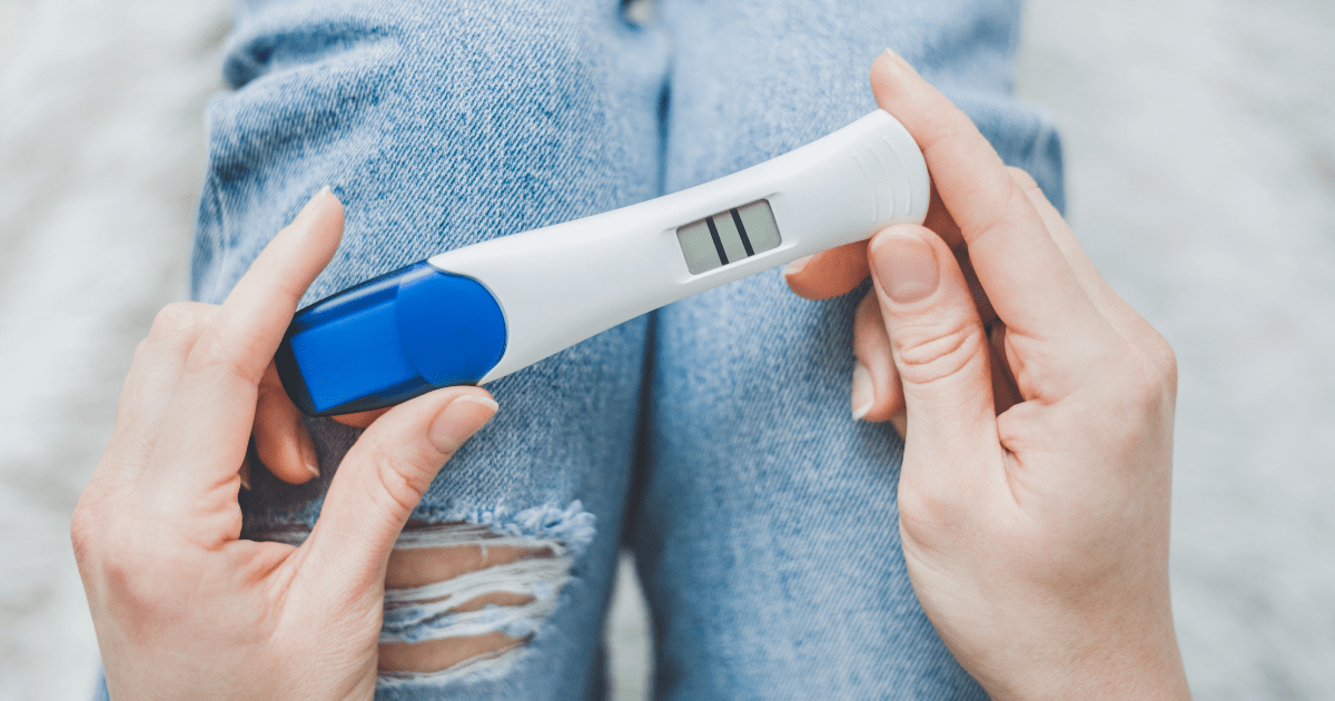 IVF: A person holding a blue and white pregnancy test looks down a positive result of two lines across a screen.