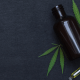 Trigeminal Neuralgia: A bottle of CBD oil against a dark background with two cannabis leaves beside it.
