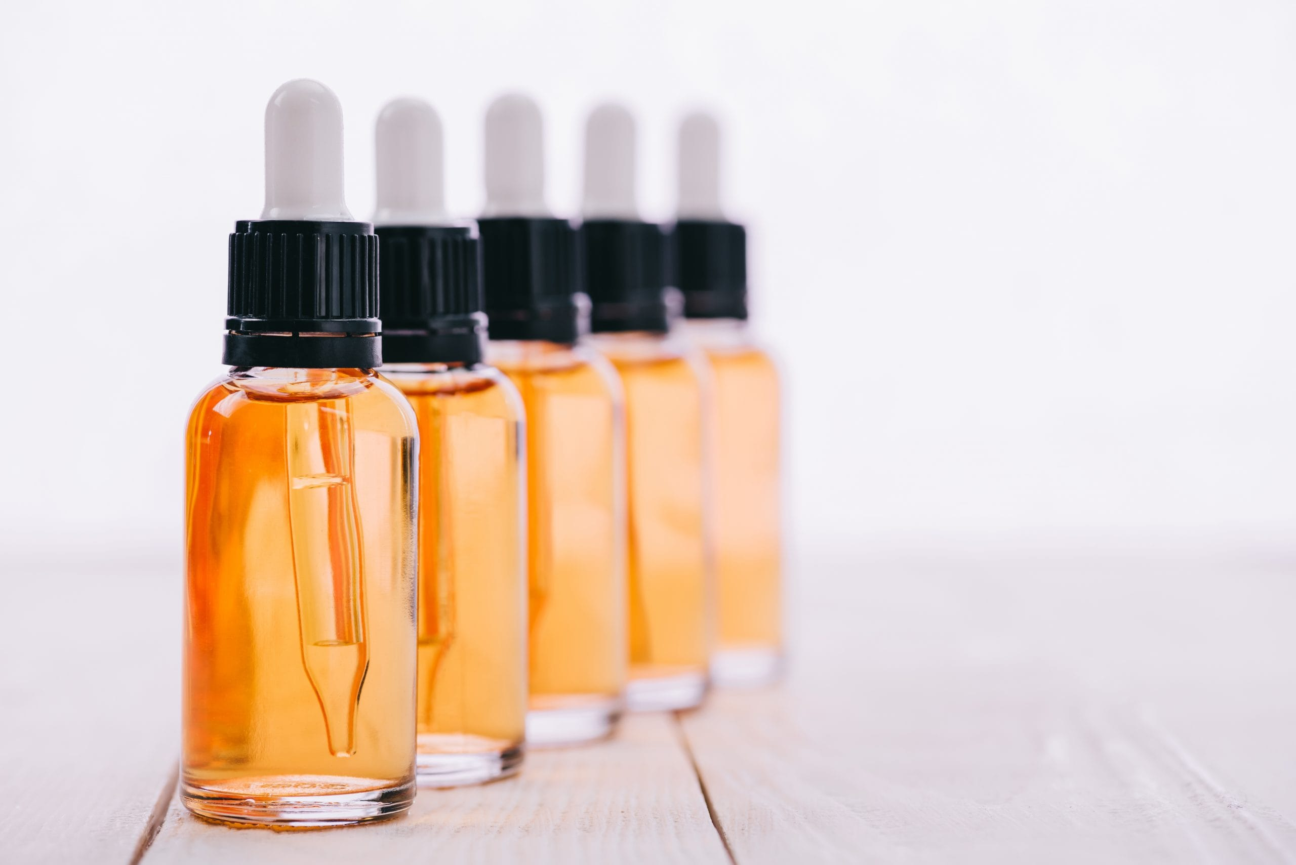 Clint Eastwood: A row of glass bottles with yellow CBD oil them