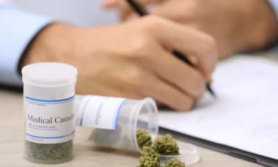 GROW: A doctor writing a medical cannabis prescription with an open canister of cannabis beside their hand