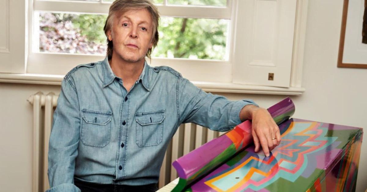Paul McCartney: The Beatles musician wearing a denim blue shirt poses next to a multicoloured artwork