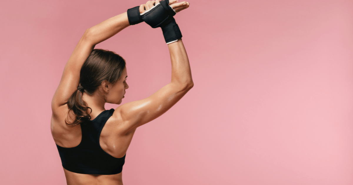 Sports: A woman stretches her arms above her head while warming up